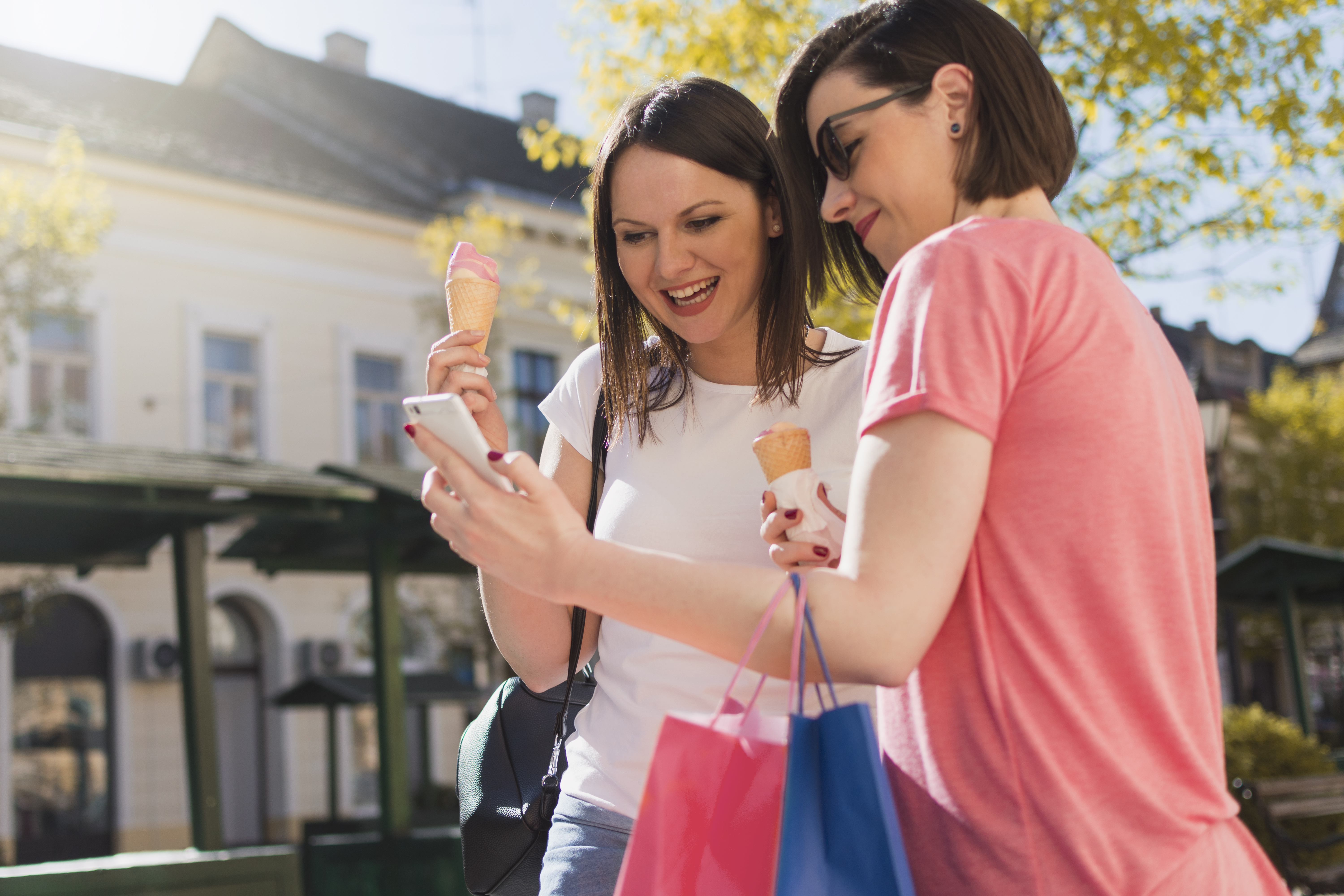 Two adult girls on mobile phone enjoy ice cream and use a cell phone while walking in city street